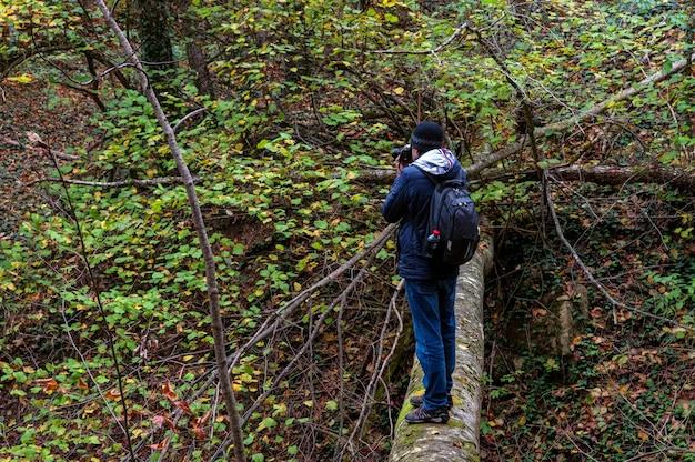 Viajante com uma câmera na floresta de outono