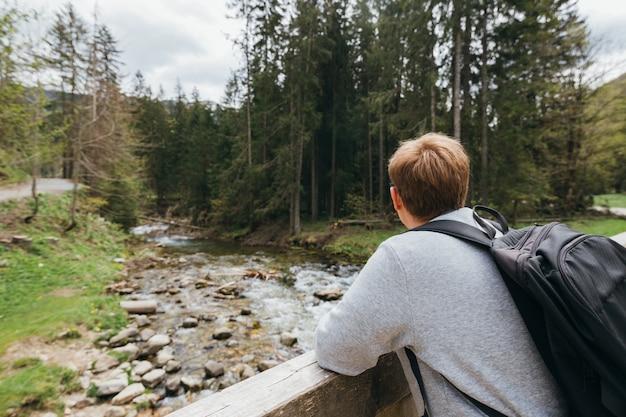 Viajante com uma mochila nas montanhas fica em uma ponte de madeira na natureza selvagem