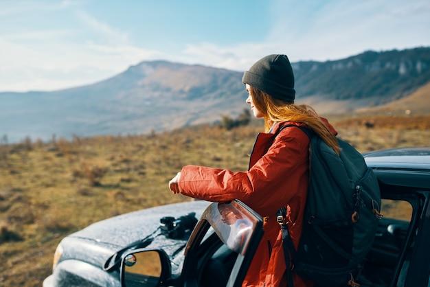 Viajante com uma mochila perto do carro nas montanhas no verão e ar fresco no céu azul