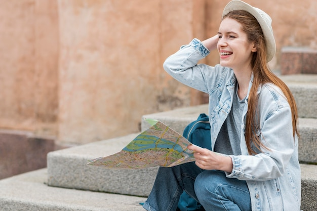 Viajante da cidade segurando um mapa e sentado na escada