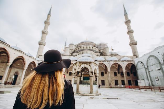 Viajante da jovem mulher no chapéu e no casaco preto que olham a mesquita azul em istambul, turquia. uma garota caminha pelo inverno istambul. foto de loira de viagens no fundo de uma mesquita no dia de outono.