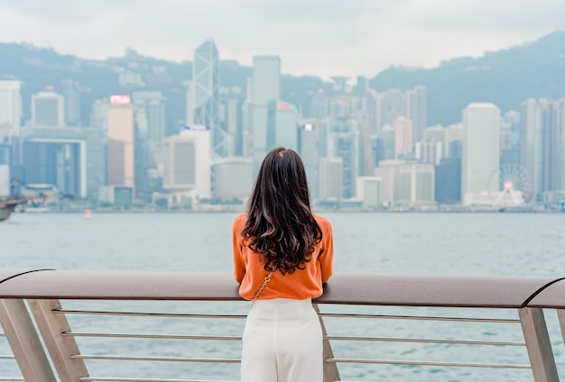 Viajante da jovem mulher que aprecia na baixa da arquitetura da cidade de hong kong sobre o porto de victoria