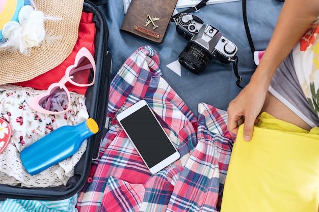 Viajante da jovem mulher que embala sua roupa e material na mala de viagem, curso e conceito das férias