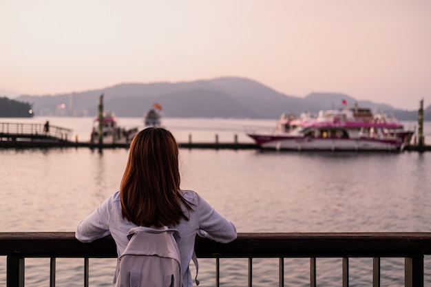 Viajante da jovem mulher que olha a paisagem bonita no lago da lua do sol em formosa, conceito do estilo de vida do curso