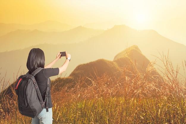 Viajante da jovem mulher que toma a foto das montanhas no por do sol conceito da vida e do estilo de vida.