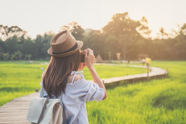 Viajante da jovem mulher que toma uma foto no campo de almofada verde bonito