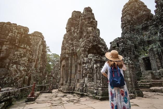 Viajante da jovem mulher que visita no templo de bayon no complexo de angkor wat