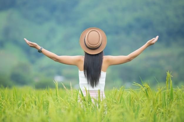 Viajante da mulher com chapéu da trouxa e vista de mentiras em um prado nas montanhas.