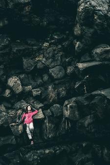 Viajante da mulher no cume rochoso em hellnar, islândia.