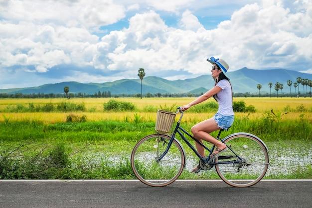 Viajante da mulher que aprecia para a vista do campo do arroz.
