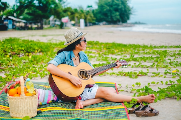 Viajante da mulher que joga uma guitarra e um piquenique na praia.