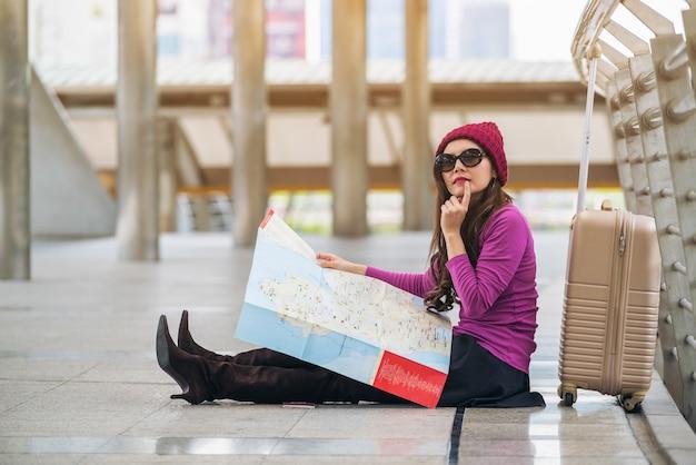 Viajante da mulher que olha o mapa do curso na passagem do aeroporto com saco ou bagagem.