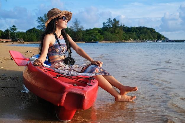 Viajante da mulher que senta-se no barco do caiaque e que toma a foto para a vista do mar em férias.