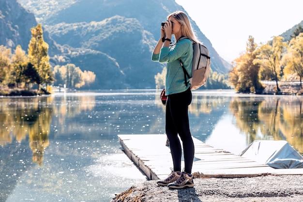 Viajante de bela jovem com mochila tirando fotos com a câmera no lago.
