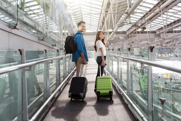 Viajante de casal asiático com malas no aeroporto