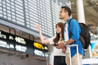 Viajante de casal asiático segurando o telefone móvel inteligente