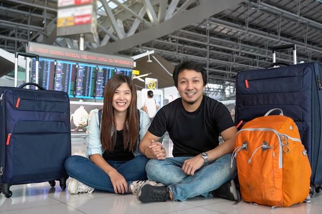 Viajante de casal asiático sentado com a bagagem sobre a placa de voo para o check-in