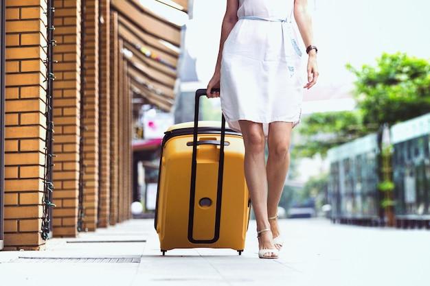 Viajante de garota e sua bagagem amarela. viagem maravilhosa