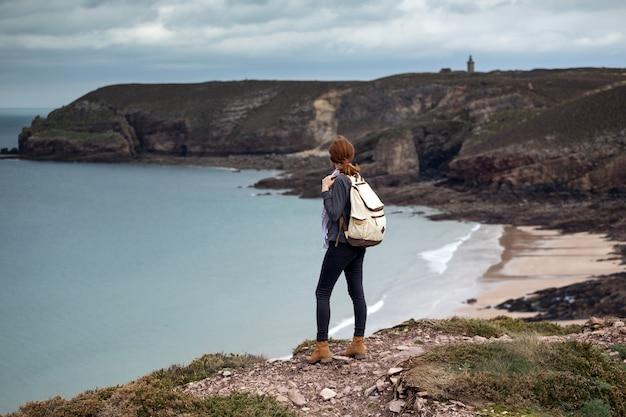 Viajante de garota no fundo cap frehel. costa típica da bretanha no norte da frança