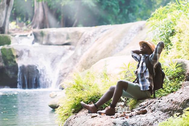Viajante de homem africano com mochila sentado e relaxante liberdade na cachoeira