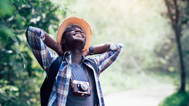 Viajante de homem africano sorrir e relaxar na selva