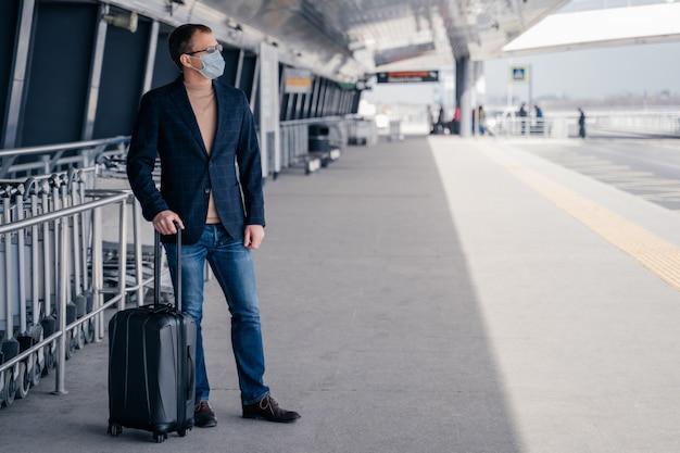 Viajante de homem com mala usa máscara protetora