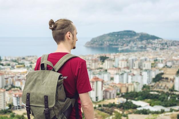 Viajante de homem com mochila explora a cidade olhando a vista panorâmica da cidade e da costa.