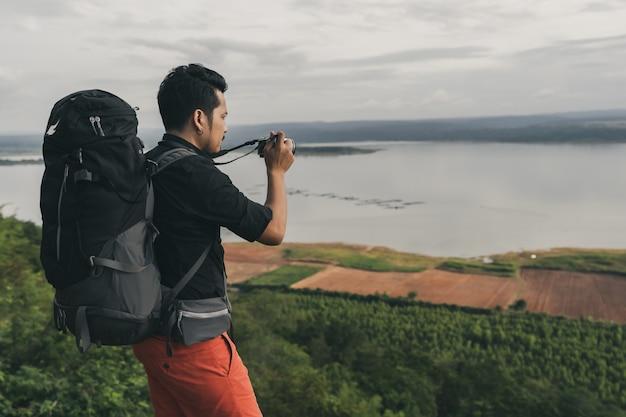 Viajante de homem com mochila usando a câmera tirando uma foto na beira do precipício, no topo da montanha de pedra
