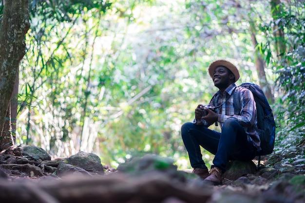 Viajante de homem de liberdade africana segurando a câmera com mochila sentado na floresta verde natural.