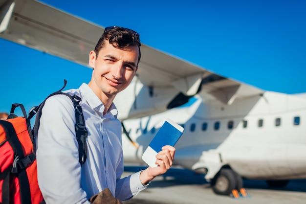 Viajante de homem embarcando no avião segurando o passaporte. feliz passageiro com mochila saindo de férias