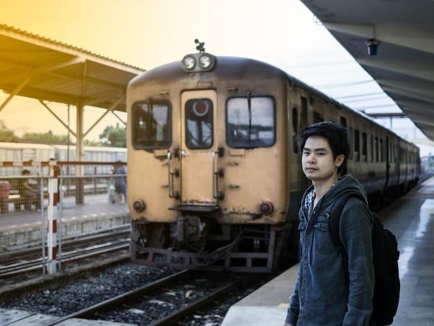 Viajante de homem ficar na estação de trem, esperando por alguém