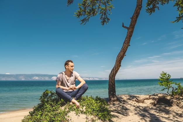 Viajante de homem relaxante na praia da ilha de olkhon, com vista para a água do lago e as montanhas e o céu azul