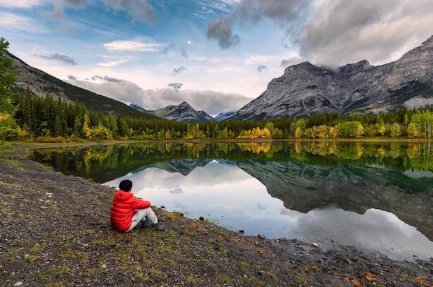 Viajante de homem relaxante no lago wedge de manhã no país de kananaskis