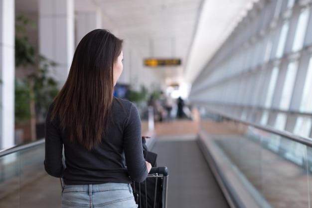 Viajante de jovem caminhando na escada rolante com carrinho de bagagem no aeroporto