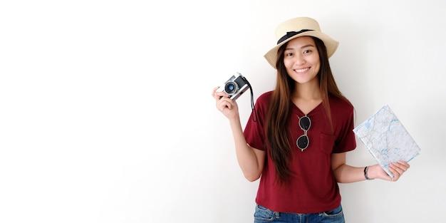 Viajante de jovem mulher asiática segurando a câmera vintage e mapa