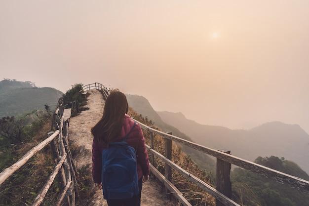 Viajante de jovem mulher olhando o pôr do sol sobre a montanha