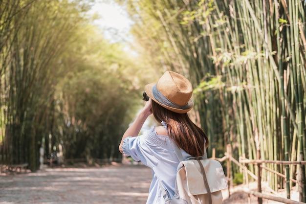 Viajante de jovem mulher tirando uma foto no belo bosque de bambu