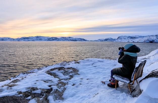 Viajante de jovens mulheres tirando uma foto na praia do mar de barents ao pôr do sol, teriberka, região de murmansk, rússia