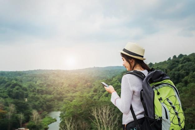 Viajante de linda mulher asiática com mochila relaxante em férias na montanha com o uso de móvel