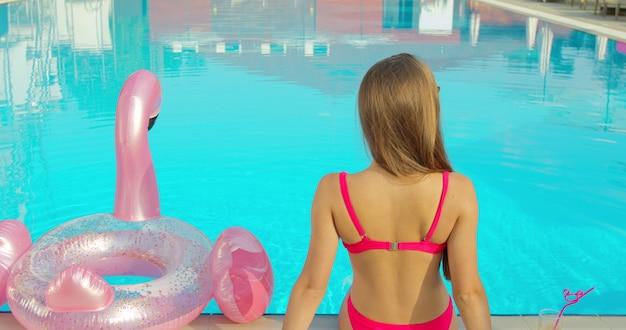 Viajante de luxo mulher sentado à beira da piscina com bebida, aproveitando o dia de verão, ficando bronzeado relaxante com tubo inflável flamingo rosa.