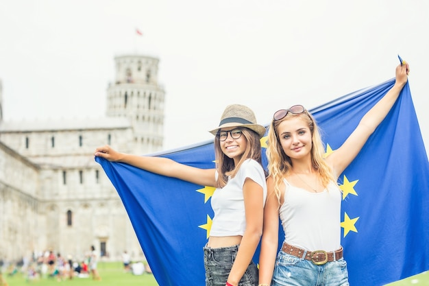 Viajante de meninas adolescentes com bandeira da união europeia antes da torre histórica na cidade de pisa - itália.