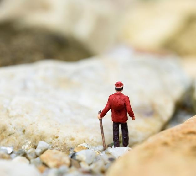 Viajante de mochila em miniatura caminhando na rocha sozinho, conceito de viagem