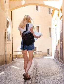 Viajante de mulher andando pela arcada na cidade histórica europeia. menina hippie viajando com mapa na europa.