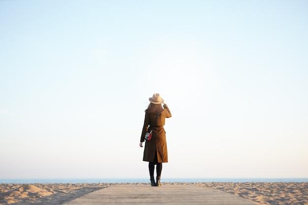 Viajante de mulher, apreciando a vista do mar calmo no outono ou primavera outwear olhando para a distância.