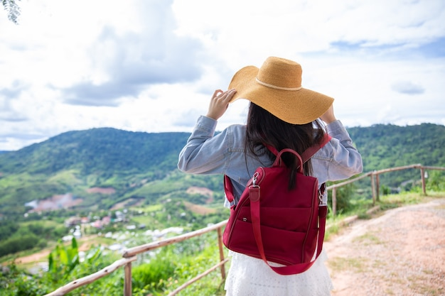 Viajante de mulher asiática com uma mochila segurando um chapéu e olhando as montanhas e a floresta