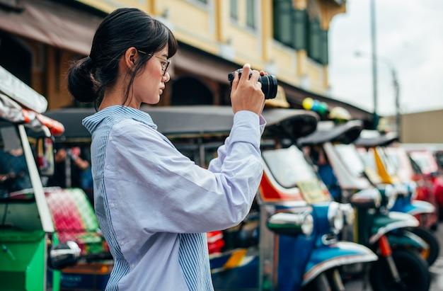 Viajante de mulher asiática usa câmera digital tira foto com fundo de carro colorido tuk tuks