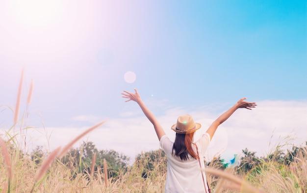 Viajante de mulher com câmera segurando o chapéu e respirando no campo das gramíneas e da floresta, conceito de viagens de wanderlust, espaço para o texto, momento épico atmosférico
