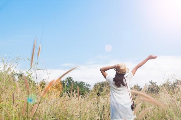 Viajante de mulher com câmera segurando o chapéu e respirando no campo de gramíneas e floresta, conceito de viagens de wanderlust, espaço para texto, momento épico atmosférico