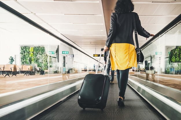Viajante de mulher com mala de viagem ou bagagem andando na passarela do terminal do aeroporto para viagens de férias no exterior. conceito de viagens ao redor do mundo, turismo. morena de saia amarela vai na escada rolante.