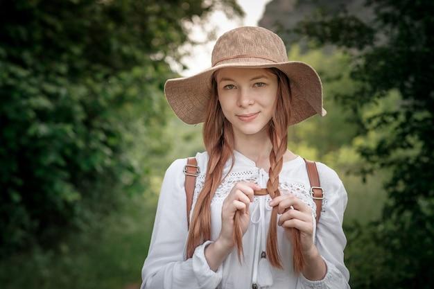 Viajante de mulher com mochila e chapéu andando em incríveis montanhas e florestas, conceito de viagens wanderlust, espaço para texto, momento atmosférico. dia da terra
